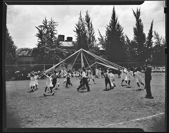 Action shot of children in festive clothing dancing around a may-pole, streamers in hand.