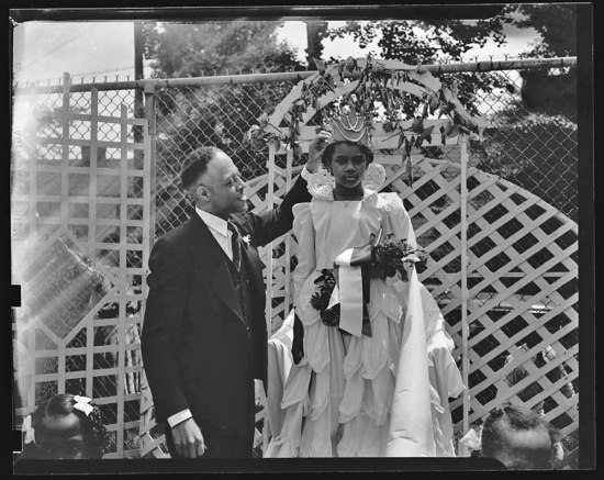 Photograph of young girl in white dress being crowned May Queen. She holds a bouquet of flowers and a man in a suit places a crown on her head.