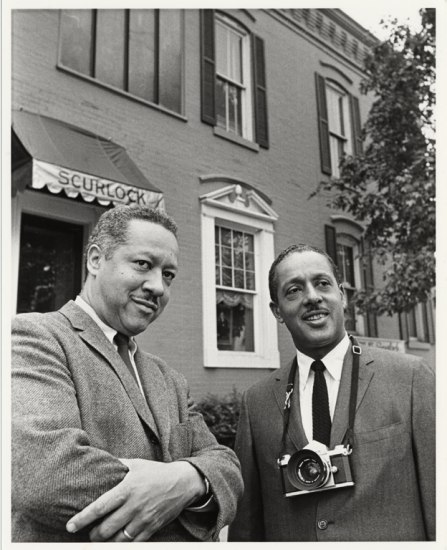 Two men stand in front of a store. One has his arms crossed, the other wears a camera around his neck.