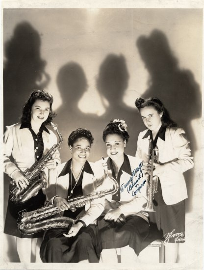 Black and white photo of four women holding instruments.