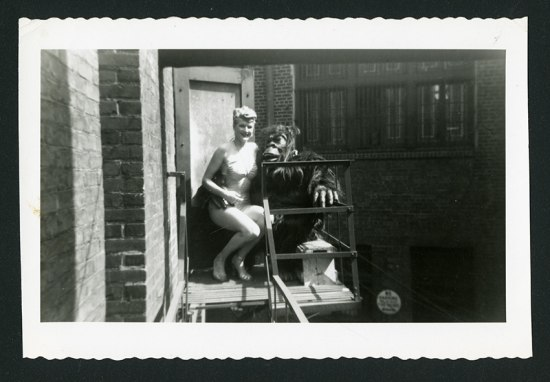 B&W photograph of a woman in lingerie sitting on a fire escape on the lap of someone in a gorilla suit