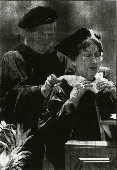 Jean Stapleton stands in college graduation robes as a university official places an honorary stole on her shoulders