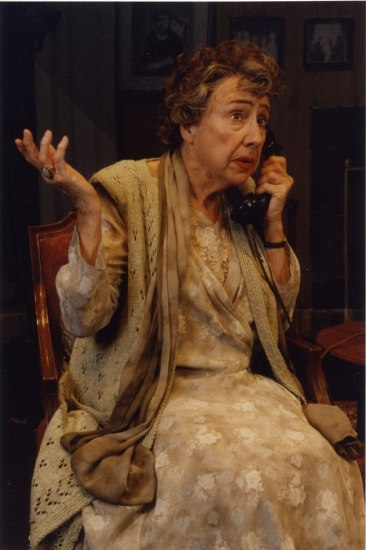 Jean Stapleton, in costume, shrugs while sitting in a chair and talking on the phone