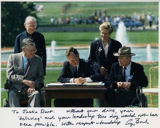 "Color photograph with green lawn and fountain in background. President Bush in center, signing documents. Two men to his left, one in a wheelchair. To his right, one man in cowboy hat in wheelchair and one woman standing. Handwritten on bottom of photo: ""To Justin Dart. Without your drive, your 'believing' and your leadership this day would not have been possible. With respect and friendship. G. Bush."""