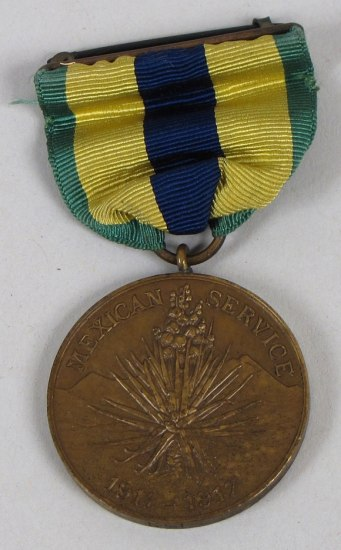 Color photo of a circular medal. Ribbon is green, yellow, and blue. Medal shows a cactus-like plant and dates 1911-1917.