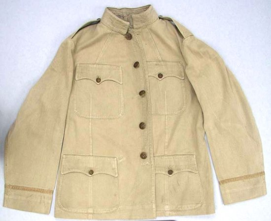 Photo of khaki colored coat. Closes down the center with five gold/brown buttons. Four pockets on front, each closed with a button. Collared.