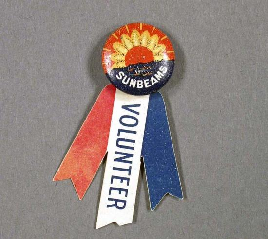 Photo of orange and blue button with three ribbons