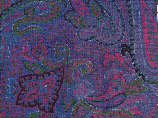 A piece of silk with a paisley and floral pattern on it. The background is a rich blue and the designs are from fuschia, green, black, and white threads.