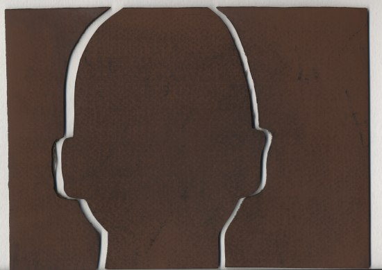 A deep brown substance with lines cut out of it in the shape of a head