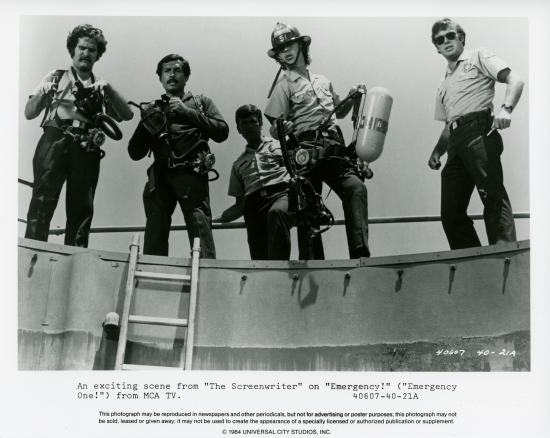 Black and white photo of actors on set, mid-scene