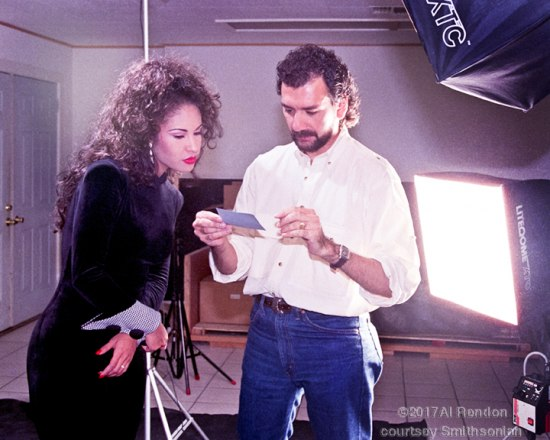 Selena and Rendon look at a photograph in a studio.