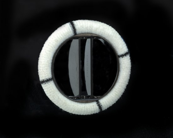 "A ring, presumably made of metal, covered in some sort of white fabric. The inner portion of the valve consists of two flipper or vent-like pieces of dark material, one of which says ""DEMO"" on it."