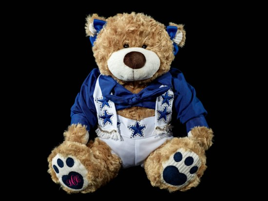 A stuffed bear toy wearing a variation of the Dallas Cowboys Cheerleaders costume, along with blue bows on its ears