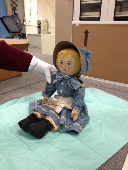 "A photograph of curator Nancy Davis preparing ""Abigail"" doll for display in the ""American Enterprise"" exhibition."