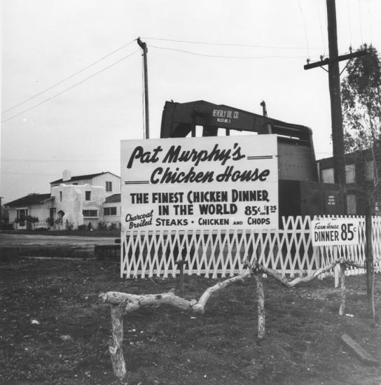 Painted sign above a white fence advertising a chicken house