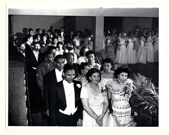 A group of people is ready to make a procession, standing three abreast in a line that curves around a room with at least one column. They are in formal attire, with corsages and bow ties and the ladies in floor-length dresses. A woman in the front row and smiles and looks right at the photographer's lens.