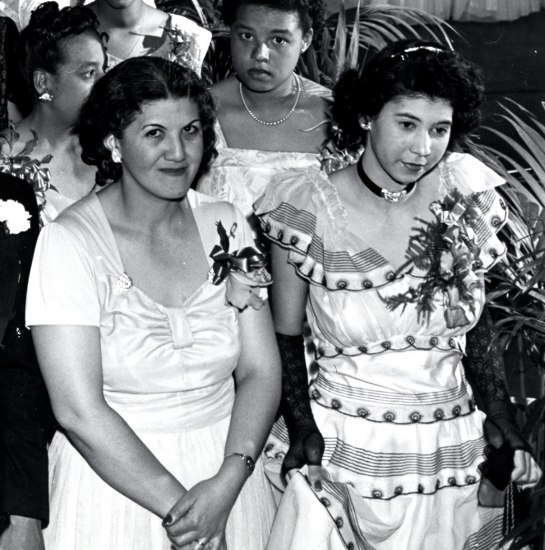 Detail of image. Chaperones and young women stand in line. One chaperone looks intently at the camera with a partial smile.