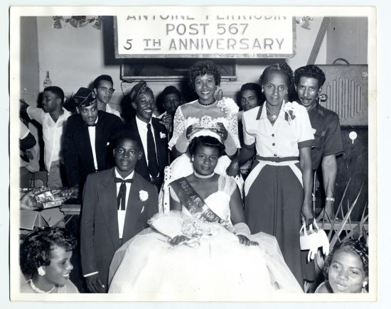 "Black and white photo of a young lady wish a sash saying ""Miss American Legion..."" is crowned with a sparkly tiara but another smiling woman. Both are in fancy dresses. Around them, men (some wearing matching uniform hats) and women smile, chat, and pose, in a blend of posed and casual modes. A sign above says ""Post 567 5th Anniversary."""