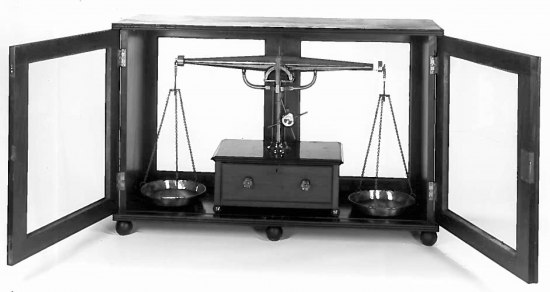 Black and white photo of a balance. Two central arms hold a plate/tray on each side. The entire thing is in a cabinet that appears to open and close.