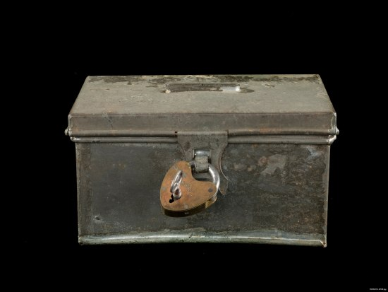 A beat up gray metal box with a rusting padlock