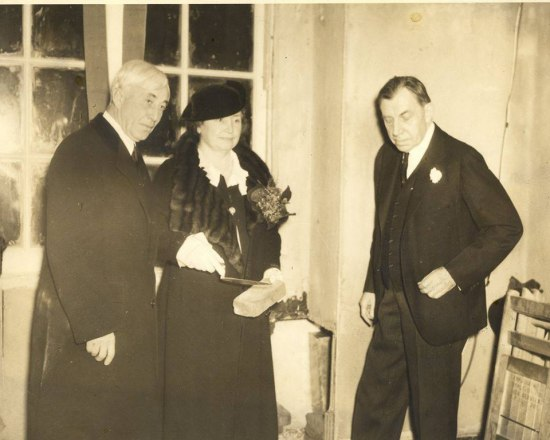 In this black and white photo, two men and one woman stand together. They are in formal attire. The woman holds a brick and a mason's tool in her hand.