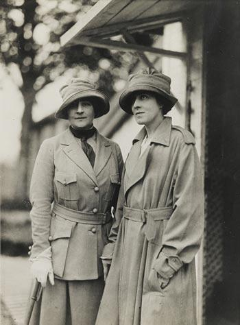 Two women in hats and trenchcoats