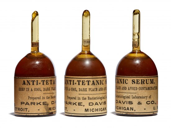 Three amber-colored bottles that resemble upside down bells with handles. They have yellowed labels on them.