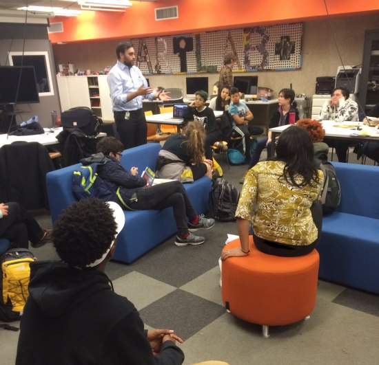 "Photo of a room in which about 12 teenagers are gathered. A man speaks to them while they listen, flip through a comic book, etc. In background, ""ArtLab+"" collaged on wall."