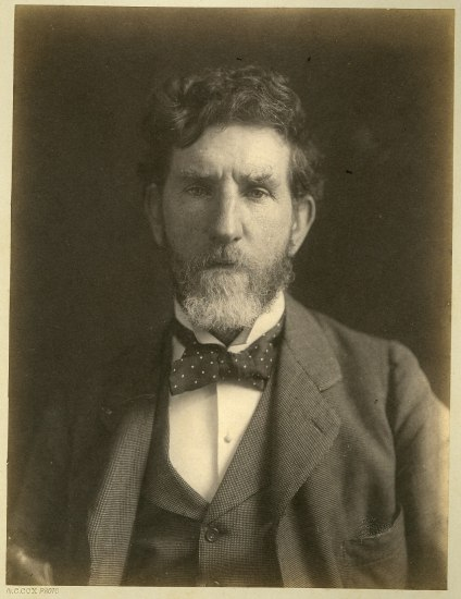 A black and white portrait of a man in a beard with a jacket and tie looking towards the camera, but slightly below so he appears to be thinking.