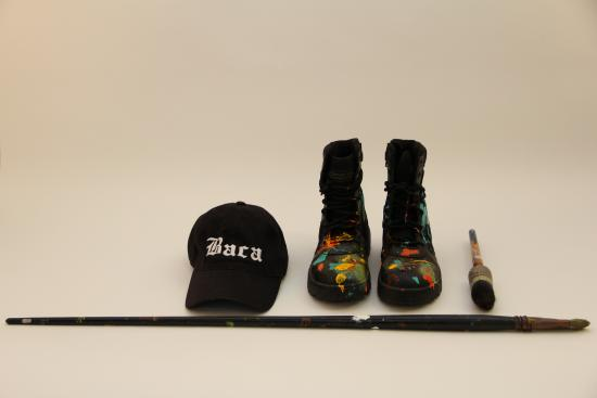 Photograph of baseball cap, work boots, and brushes