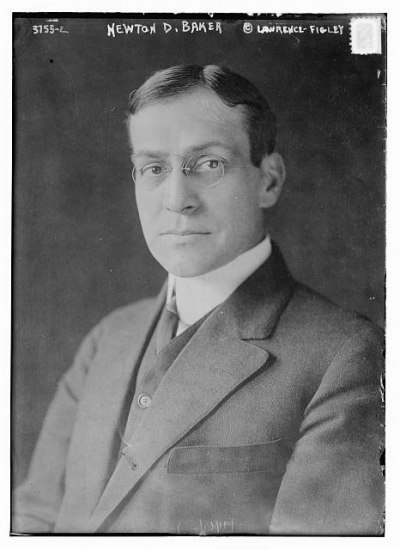 Black and white portrait of a man. He looks at the camera and wears glasses.