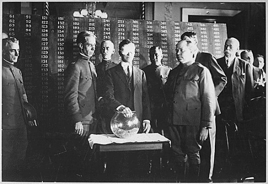 Black and white photo. In front of what appear to be tall storage cabinets with small, numbered drawers, a blindfolded man picks something out of a glass bowl. Other men watch.