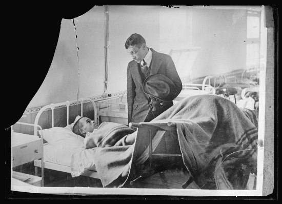 Black and white photo of one man visiting another in hospital. One man lays in bed, looking up at visitor. The other looks down, chatting, holding hat.