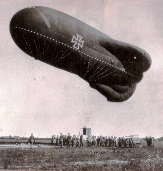 Men stand on the ground under a large inflated balloon