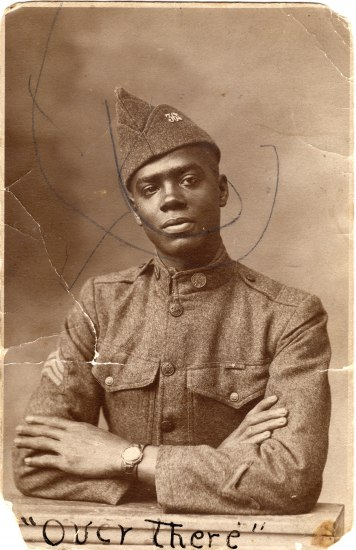 Black and white photo of an African American man in military uniform. His arms are gently crossed, a watch o his wrist. His head is slightly tilted to the right, with a serious but gentle look on his face. The uniform has pockets, buttons, and a fairly hi