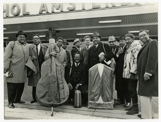 Black and white photo: Twelve men in coats and some in hats stand outside the airport, some holding instrument cases.