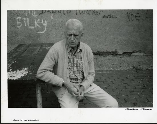 A white-haired man sits with his elbow resting on a weathered table looking away from the camera. Behind him is a wall with some graffiti.