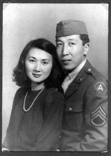 A black and white picture in which a man in a military uniform sits with a woman sitting in front of him, wearing a black shirt and pearls. It is a more formal, staged picture.