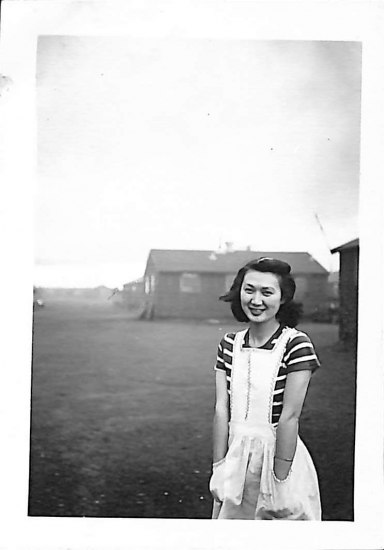 black and white photograph of a woman standing outside. She wears a striped top under a white jumper with large pockets she sticks her hands into. She smiles at the camera with a small house in the background.