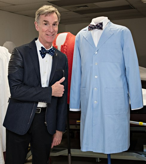 "Photo of man giving ""thumbs up"" signal wearing black jacket, white shirt, black bow tie. He is beside a blue lab coat on a mannequin."