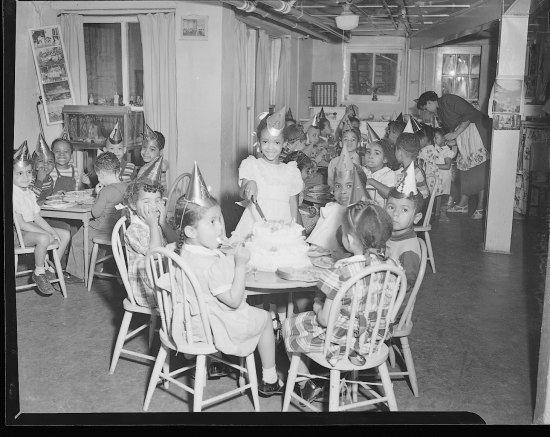 In what looks like a basement room, children celebrate a birthday party, wearing party hats and sitting at chairs with cake in front of each kid. The birthday girl slices the cake. Meanwhile, an adult wearing an apron helps another child keep her hat on her head. Many of the girls have pigtails. One or two make a big smile or silly face.