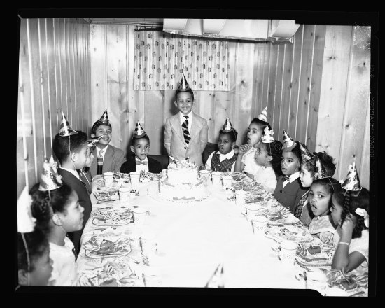 Indoor black and white photo of children gathered around a rectangular table, wearing party hats and waiting to eat cake. The birthday boy, in suit and tie, grins, standing with his hands behind his back with his two-tiered cake in front of him. Behind him, a patterned curtain. Wood-paneled room.