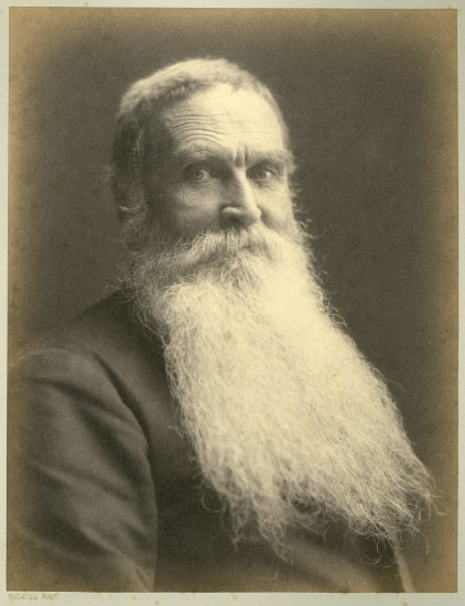 A portrait of a man with a long white beard who looks straight into the camera while seated at an angle.