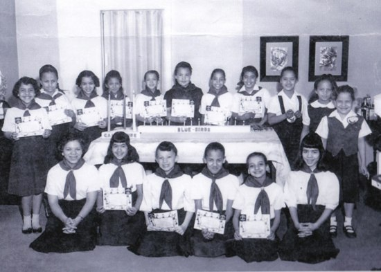 A group of girls in uniform stand around a table holding their certificates.