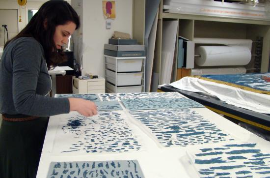 A woman in a blue sweater stands in front of a table covered in white material with small pieces of blue fabric