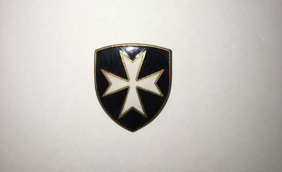 A shield-shaped medal. The background is a shiny black lacquer and there is a white cross in the center