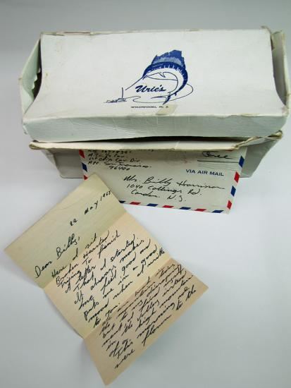 Battered white shoe box with letters in black script in front