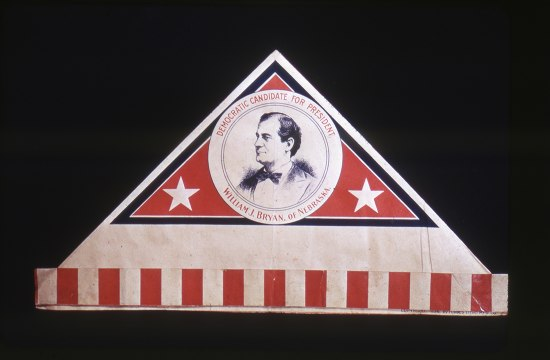 "A paper hat lying flat. The cap portion is triangular like a hat one would make from folded newspaper. The ""brim"" is vertical red and white stripes. There is a pattern on the cap and within it is a picture of ""Democratic Candidate for President, William J. Bryan, of Nebraska"""