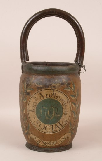 "A brown bucket with a handle and a green circle saying ""'79"" ringed by a cream band reading ""Jon Andrew Social"""