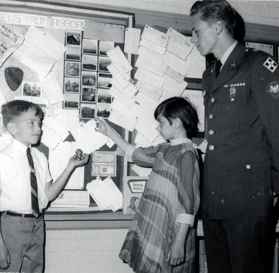 Black and white photo of a young boy and girl, looking at a bulletin board, with a uniformed soldier